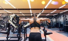 Woman flexing muscles on cable machine in gym. Sport, fitness, bodybuilding, lifestyle and people concept - woman flexing muscles on cable machine in gym Royalty Free Stock Image