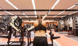 Woman flexing muscles on cable machine in gym. Sport, fitness, bodybuilding, lifestyle and people concept - woman flexing muscles on cable machine in gym Stock Photos