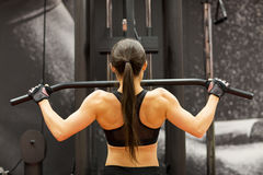 Woman flexing muscles on cable machine in gym Stock Image