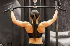 Woman flexing muscles on cable machine in gym. Sport, fitness, bodybuilding, lifestyle and people concept - woman flexing muscles on cable machine in gym Royalty Free Stock Photography