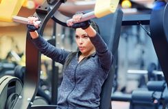 Woman flexing muscles on chest press gym machine. Fitness, sport, bodybuilding, exercising and people concept - young woman flexing muscles on seated chest press Stock Photo