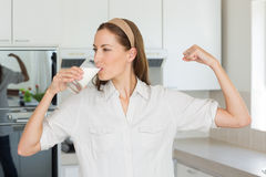 Woman flexing muscles while drinking milk in kitchen. Young woman flexing muscles while drinking milk in the kitchen at home Stock Image