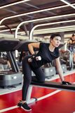 Woman flexing muscles with dumbbell on bench in gym. Young woman flexing muscles with dumbbell on bench in gym Royalty Free Stock Photo