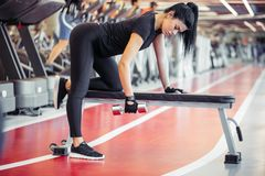 Woman flexing muscles with dumbbell on bench in gym. Young woman flexing muscles with dumbbell on bench in gym Stock Photo