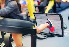 Woman flexing muscles on leg press machine in gym. Fitness, sport, bodybuilding, exercising and people concept - close up of young woman flexing muscles on leg Stock Photos