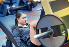 Woman flexing muscles on leg press machine in gym. Fitness, sport, bodybuilding, exercising and people concept - young woman flexing muscles on leg press machine Stock Photos