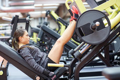 Woman flexing muscles on leg press machine in gym. Fitness, sport, bodybuilding, exercising and people concept - young woman flexing muscles on leg press machine Royalty Free Stock Images