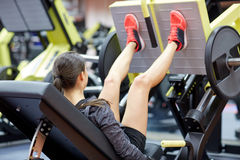 Woman flexing muscles on leg press machine in gym Royalty Free Stock Images
