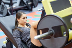 Woman flexing muscles on leg press machine in gym. Fitness, sport, bodybuilding, exercising and people concept - young woman flexing muscles on leg press machine Stock Images