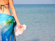 Woman with flip flops. Woman in bikini with pink flip flops by the sea royalty free stock images
