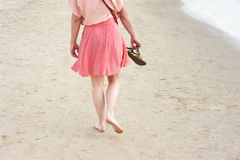 Woman with flip-flops. A young woman walking on the sand with flip-flops in hand stock photography