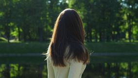 Woman flip her long shiny hair against green foliage. Smiling girl with flying hair, slow motion stock video