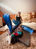 Woman in flippers holding legs on suitcase at bedr Stock Photography