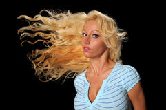 Woman Flipping Hair. Young woman flipping hair isolated over a black background Stock Photography