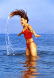 Woman flipping hair in ocean Stock Photography