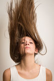 Woman flipping her hair up. Portrait of a beautiful young woman flipping her hair up in the air making it look like it's standing up. Isolated against a light Stock Photo
