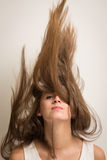 Woman flipping her hair up. Portrait of a beautiful young woman flipping her hair up in the air making it look like it's standing up. Isolated against a light Royalty Free Stock Photos