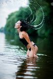 A woman flipping her wet hair making a rainbow of water with her hair. Girl standing in the water Stock Images