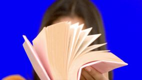 Woman flipping through a pink book on blue screen Royalty Free Stock Images