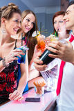 Woman flirting with barkeeper. In cocktail bar stock image