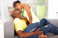 Woman flirting boyfriend. Beautiful young african women sitting on boyfriend flirting stock images