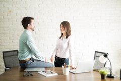 Woman flirting with her coworker. Beautiful Latin young women having an office fling with a colleague and smiling Stock Photo