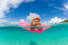Woman float raft tropical water. Woman floating on inflatable raft in tropical water with feet showing under over Stock Photo