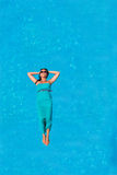 Woman floating above pool water Royalty Free Stock Photos