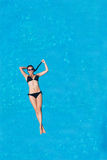 Woman floating above pool water Royalty Free Stock Photography