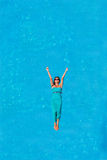 Woman floating above pool water Stock Photography