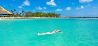 Woman floating on a back in the beautiful sea. Aruba island stock image