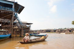 Woman floating on a boat  built on the Tonle Sap lake. Kampong, Siem Reap, Cambodia 11 December 2012: A woman floating on a boat in the village built on the Stock Photography