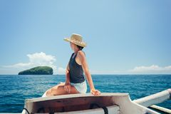Woman floating on the boat near the island in ocean. Pretty woman floating on the boat near the island in ocean Royalty Free Stock Images