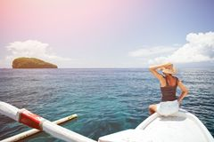 Woman floating on the boat in ocean near the island. Cheerful woman floating on the boat in ocean near the island Royalty Free Stock Photography