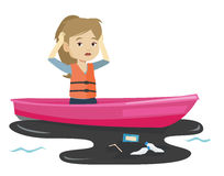 Woman floating in a boat in polluted water. Stock Photo