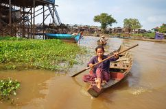 A woman floating on a boat in the village on Tonle Sap lake. Village life on the water in Cambodia 11.12.2012 Stock Photos