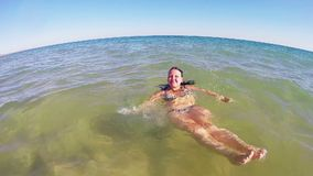 A woman is floating on her back in the sea by the coast stock footage