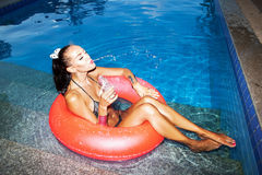 Woman floating in inner tube in pool and drinking water Stock Images