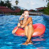 Woman floating in inner tube in pool and having fun Royalty Free Stock Image