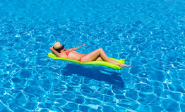 Woman floating on a mattress in a swimming pool stock images