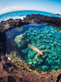Woman floating in natural pool Royalty Free Stock Photos