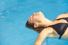 Woman floating in pool Stock Photo