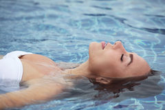 Woman floating in pool stock images