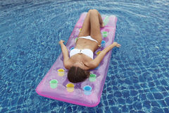 Woman floating in pool Royalty Free Stock Photos