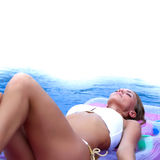 Woman floating in pool Royalty Free Stock Images