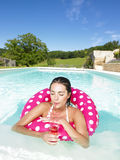 Woman Floating in Pool and Enjoying Drink Royalty Free Stock Image