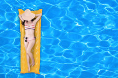 Woman floating on a pool mattress 1 Stock Image