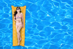 Woman floating on a pool mattress Stock Photos