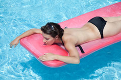 Woman floating in pool with top off. Woman in black bikini floating on stomach Stock Images