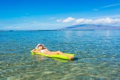 Woman floating on raft in tropical ocean Stock Image